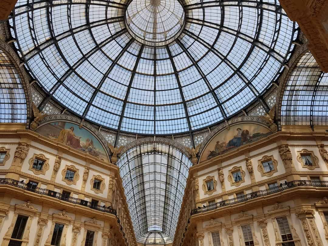 A large clock mounted to the side of Galleria Vittorio Emanuele II